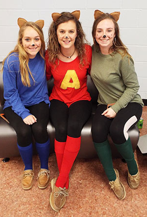 Three students sitting on a couch, dressed in feline Halloween costumes