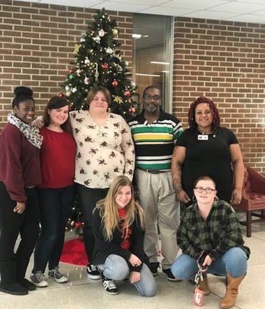 Several students lined up for a photograph in the college lobby, in front of a Christmas tree