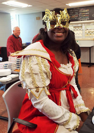 A student smiling at the camera while wearing a Halloween costume and mask